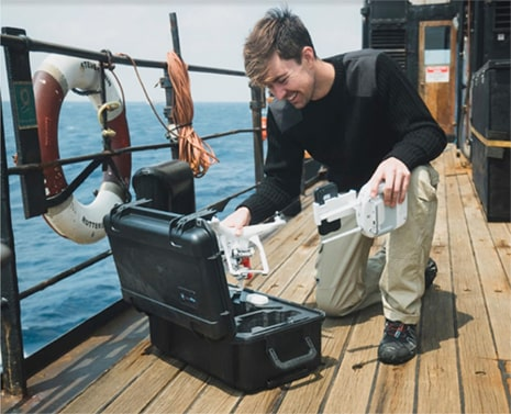 man on boat taking dji phantom out of waterproof drone case